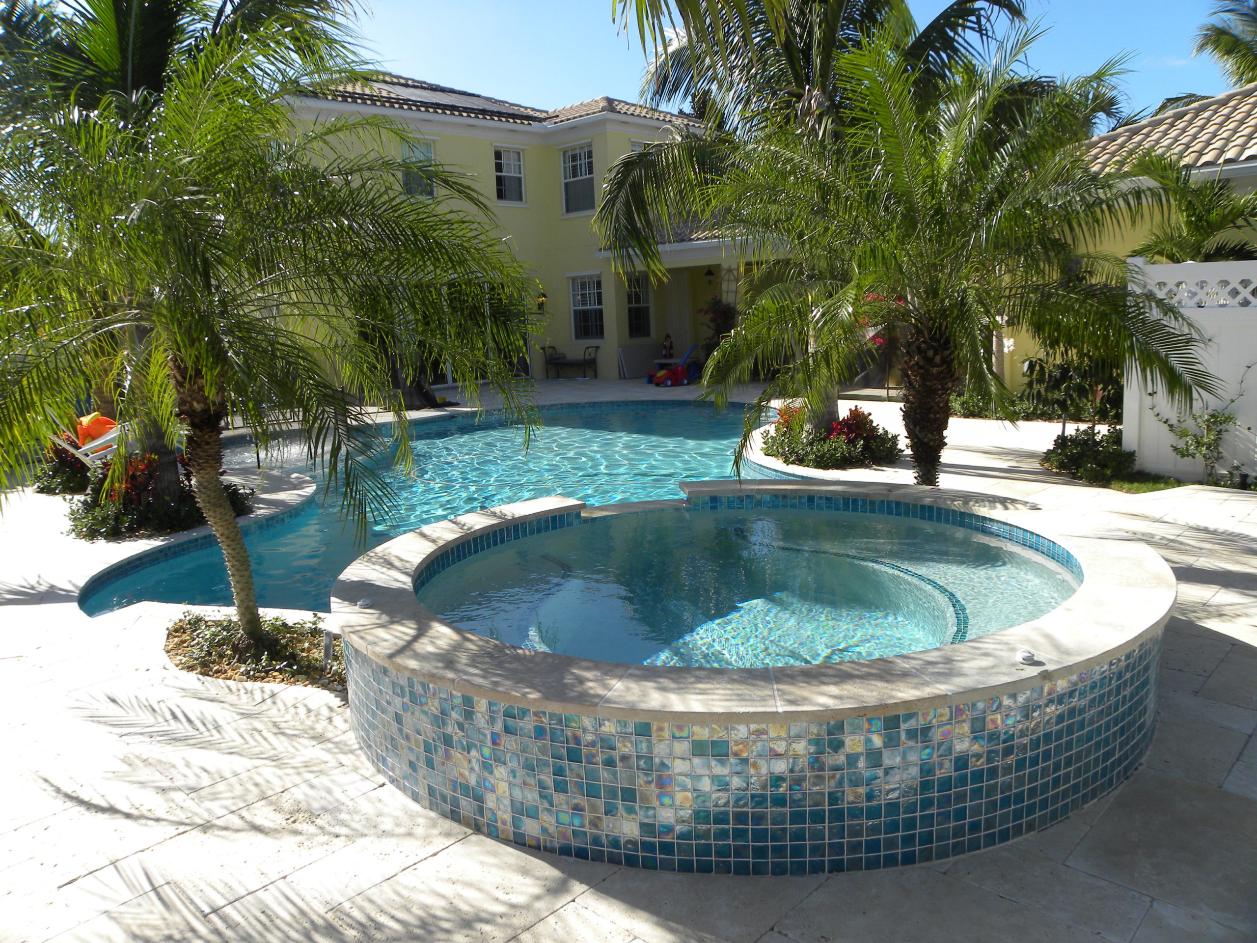 rhr pools of jupiter fl raised spa with glass tiles and organic shaped pool