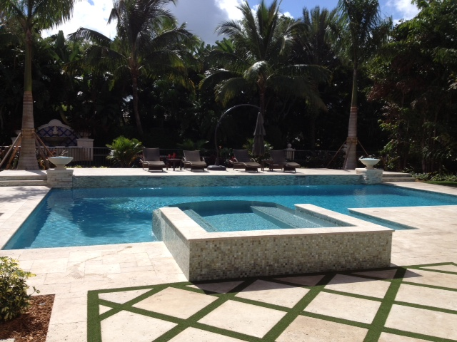 rhr pools classical shaped pool with raised spa and natural earth tones custom pool company jupiter fl