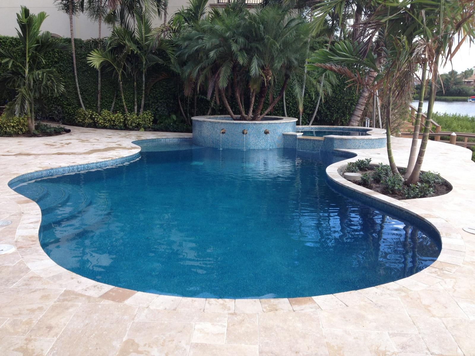 rhr pools organic shaped pool with blue interior and water feature on raised wall