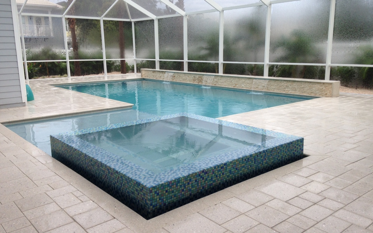 rhr pools of jupiter fl raised spa with mosaic edge, sunshelf and raised wall with water features