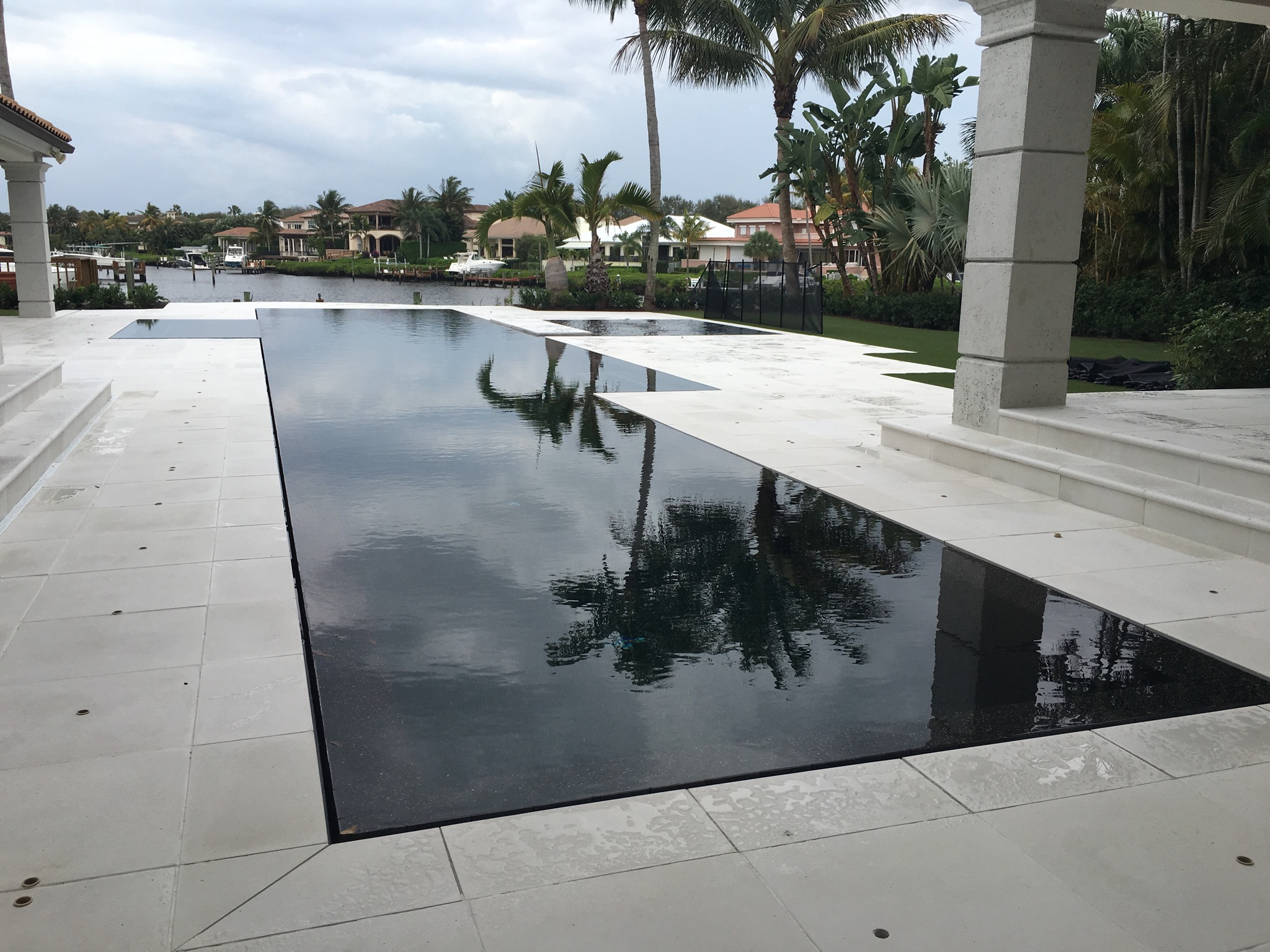 rhr pools of jupiter fl modern pool with dark interior and infinity edge overlooking the water