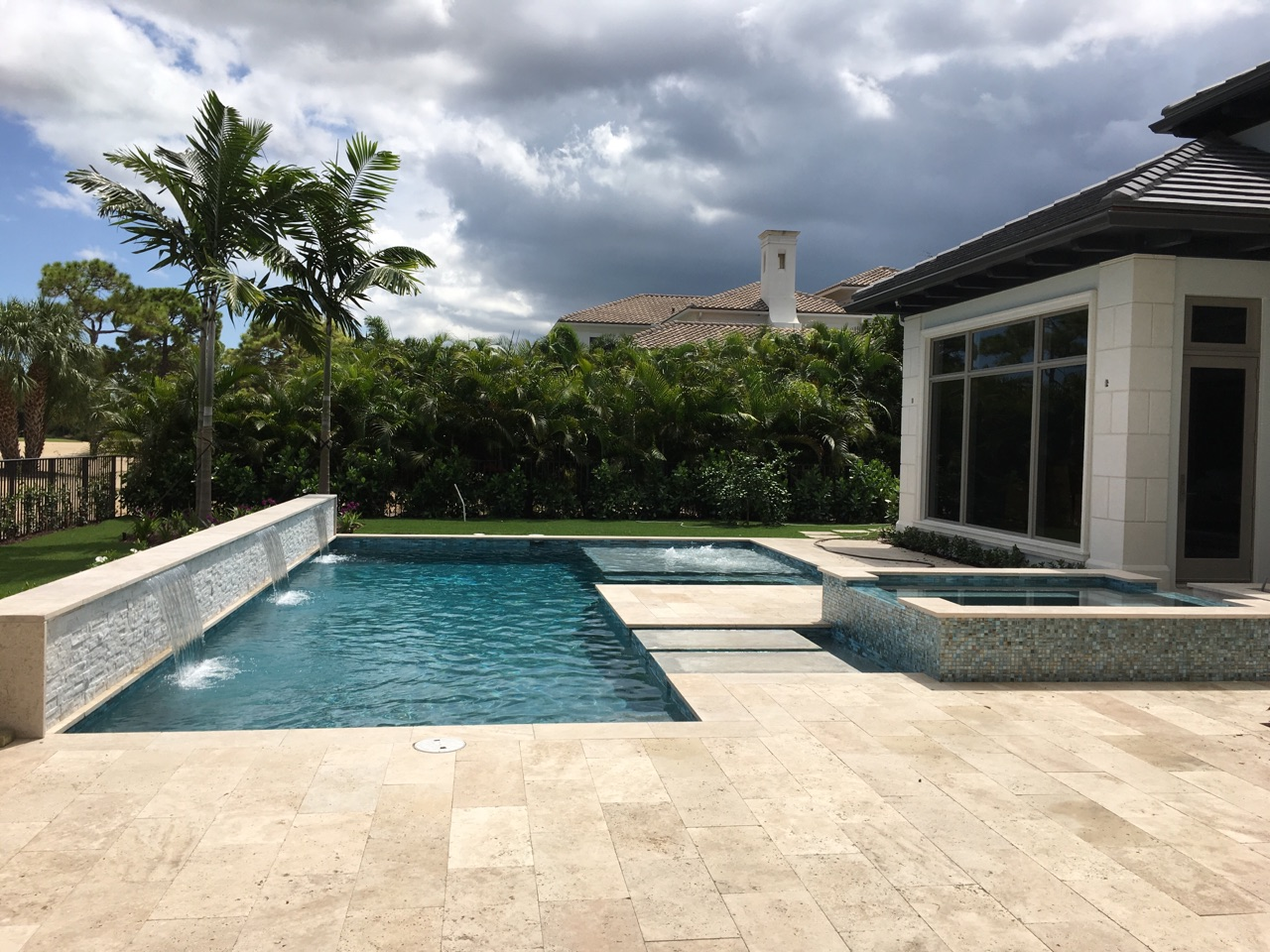 rhr pools of jupiter fl dark interior pool with raised wall and sheer decent water feature