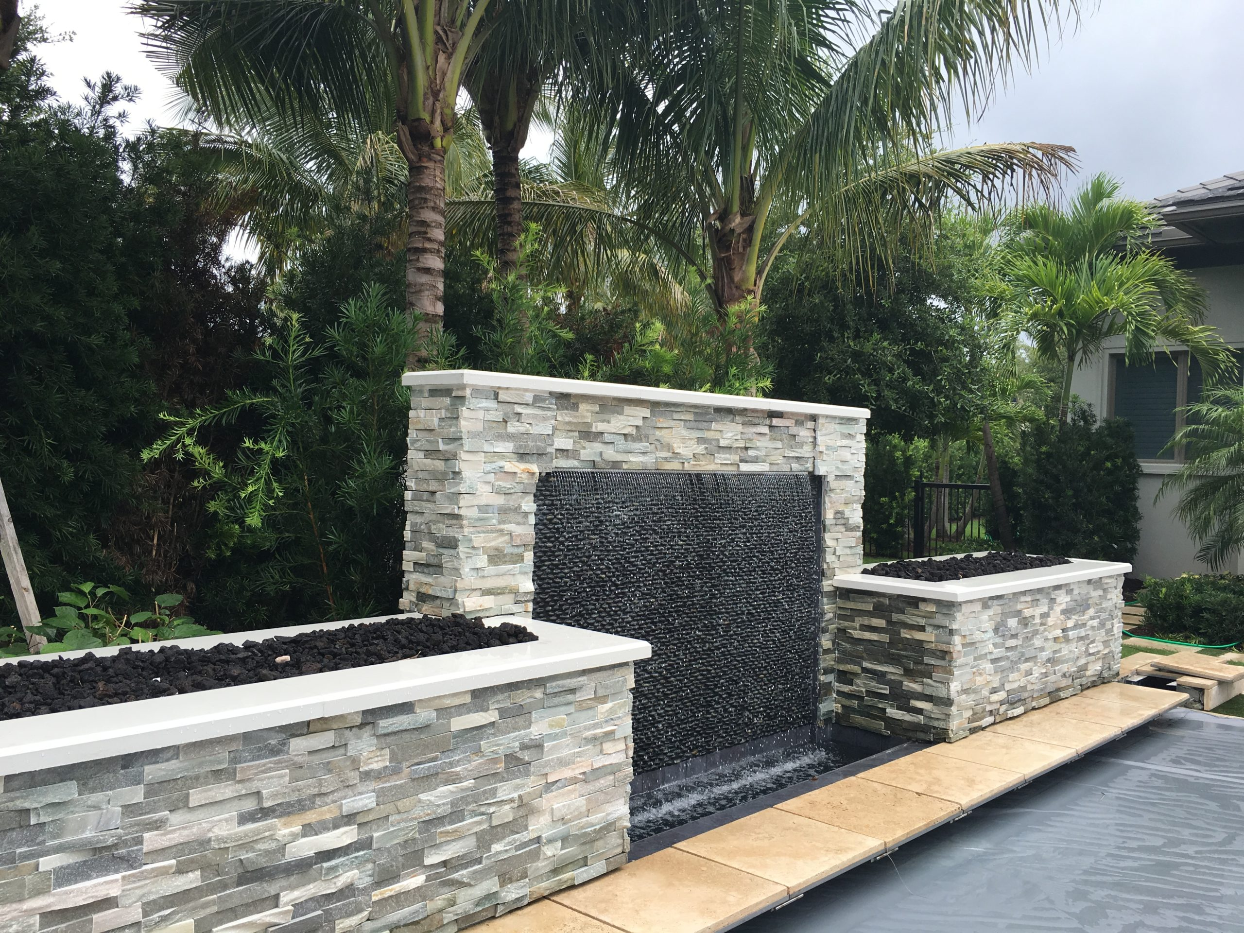 rhr pools of jupiter fl raised wall with sheer decent flanked by fire features